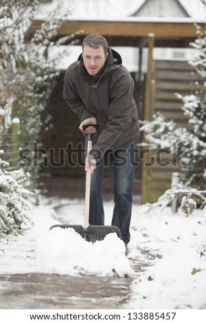 after a snowstorm. man with a black shovel to removes the snow from a house entrance.