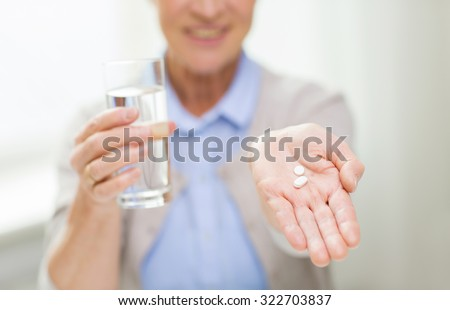 age, medicine, health care and people concept - close up of happy senior woman with pills and glass of water at home