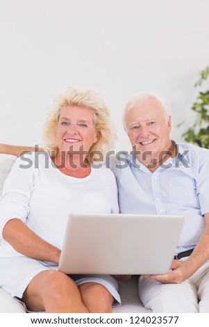Aged couple using a laptop together sitting on the sofa