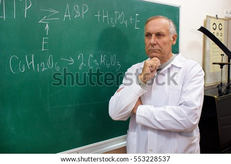 Aged professor thinking standing near the blackboard