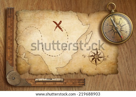 aged treasure map, ruler and old gold compass on wooden table top view