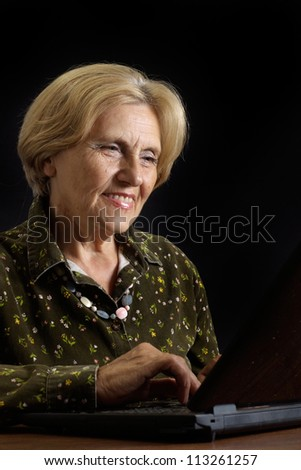 Aged woman relaxing at home on a dark background