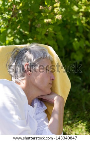 Aged woman with grey hairs sleeping on lounger in her garden.