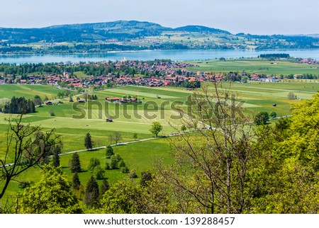 Agricultural landscape with a village, lake and mountains in Germany.