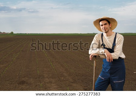 Agricultural worker posing on corn field with copy space
