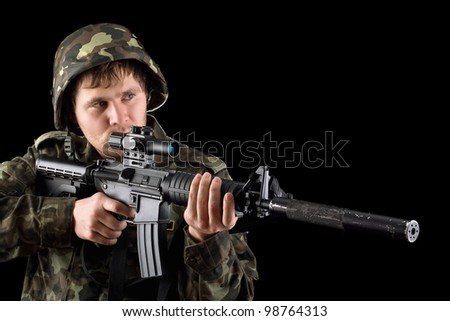 Aiming soldier with a rifle in studio. Isolated