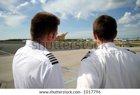 Airline pilots looking towards the runway - captain pointing
