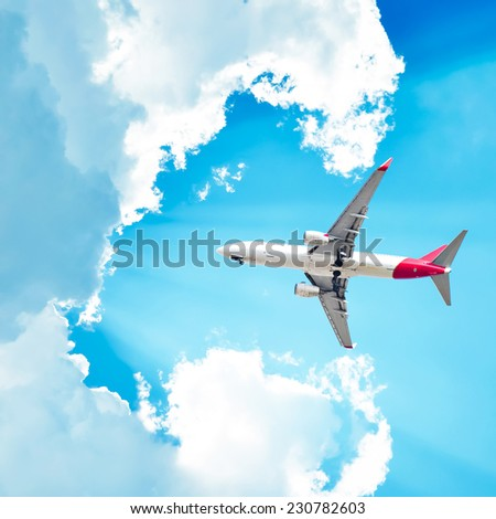 Airplane flying in sunny sky with clouds