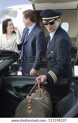 Airplane pilot putting luggage in car with business people in the background at airfield