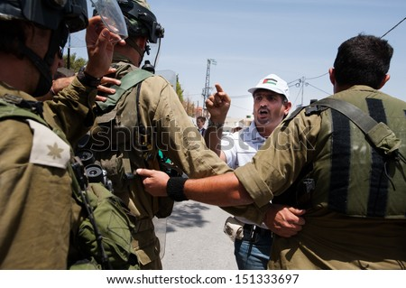AL MA'SARA, PALESTINIAN TERRITORY - MAY 24: Palestinian activists confront Israeli soldiers during a protest against the occupation and separation wall in the West Bank town Al Ma'sara, May 24, 2013.