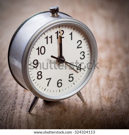 Alarm-clock on brown wooden surface showing twelve o'clock. Shallow depth of field