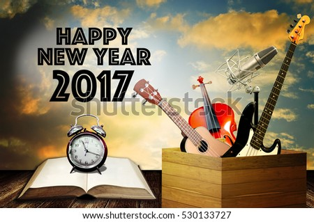 Alarm clock on open book and music instrument with happy new year greeting word