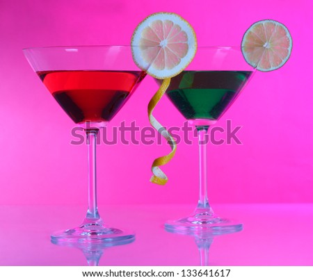 Alcoholic cocktails in martini glasses on pink background