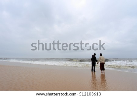 ALLEPPEY, INDIA - JUN 25:Unidentified tourists spend time in the wavy seashore on June 25, 2011 in Mararikulam beach in Alleppey,Kerala, India.