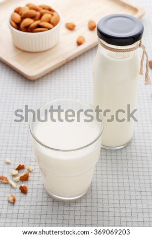 Almond milk in glass and bottle with almonds on table