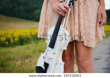Alone young woman holds violin and bow