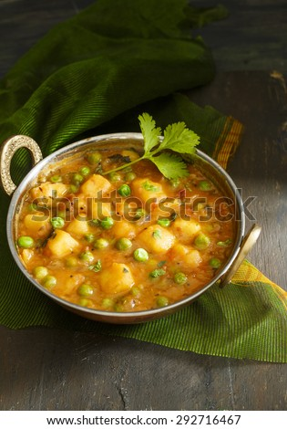 Aloo Mutter , Indian curry  Potato and Peas immersed in an Onion Tomato Gravy and garnished with coriander leaves.