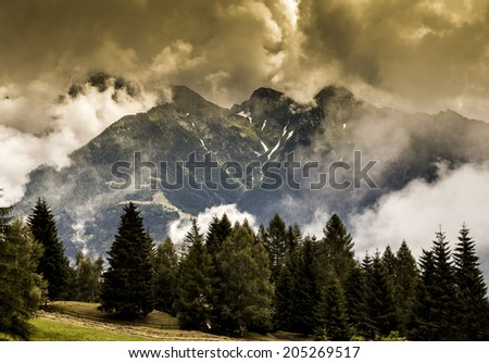 Alpine emotional sunset landscape in autumn with trees and clouds