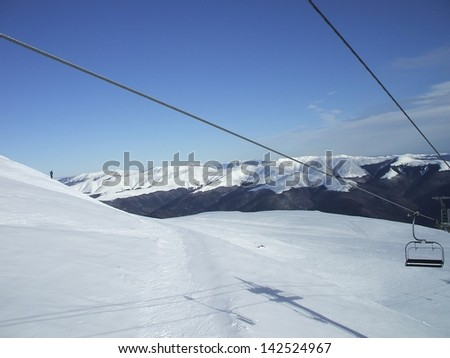 Alpine funicular over the slopes covered with snow