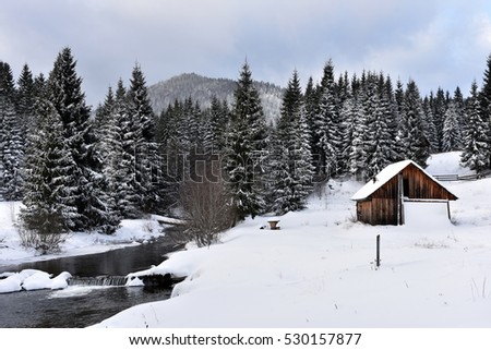 Alpine house covered with snow in the mountains at winter