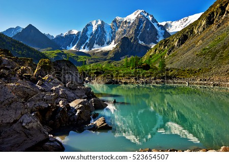 Alpine landscape. The top of the mountain are covered with glaciers flowing down to the rocky slope. Altai, Highlands region of Siberia. Lake Shavla and peaks reflecting in the water