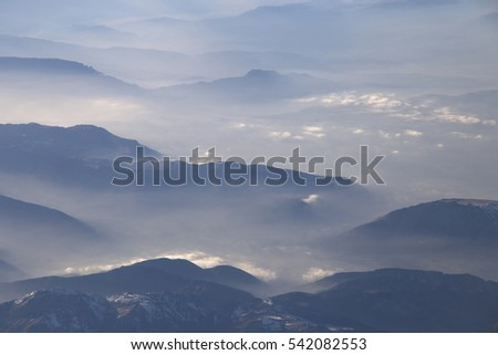 Alps mountains and Clouds from above on December