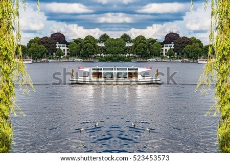 Alster Lake in Hamburg Germany on a summer day. View at famous city park Alsterwiese, located in the center of the Hansestadt Hamburg for travel concept, image with mirrored symmetry effect