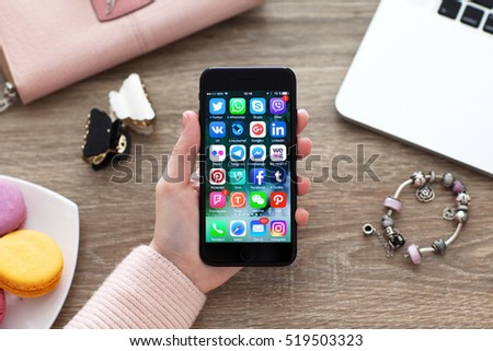 Alushta, Russia - November 17, 2016: A set of programs from famous brands of social networking on the iPhone 7 in woman hands. iPhone 7 Jet Black was created and developed by the Apple inc.