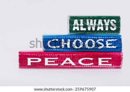 Always Choose Peace painted wooden blocks isolated on white with a rustic grunge appearance.