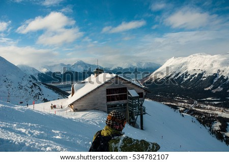 Alyeska ski resort overlook winter wonderland Editorial: March 1st 2012 A man sits and enjoys the epic view of the snowy Chugach Mountains in Alaska