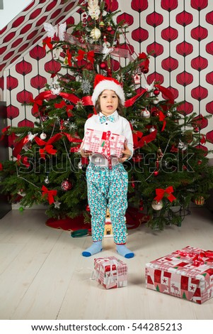 Amazed boy holding Christmas gift