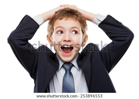 Amazed or surprised child boy in business suit hand holding hairs on head white isolated