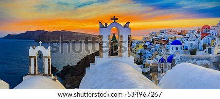 Amazing panorama sunset view with white houses in Oia village on Santorini island in Greece.