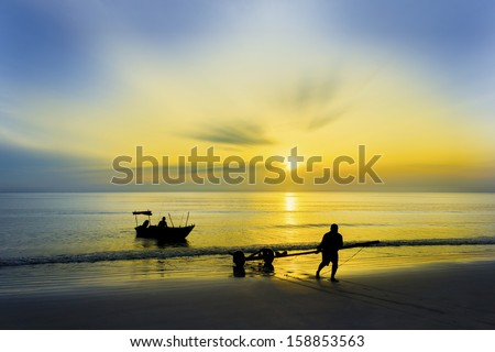 amazing sunrise and fisherman silhouette at beach