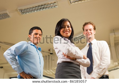 Ambitious Asian woman arms crossed looking down smiling in front of diverse business team standing, looking down at the camera at a low angle where white office ceiling visible. Horizontal copy space