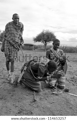 AMBOSELI, KENYA-OCT. 13: Portrait of young Maasai warriors showing how they make fire in a traditional way to guests visiting their village taken on Oct 13, 2011 in Masai Mara, Kenya.