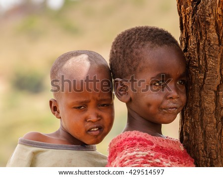 AMBOSELI, KENYA - OCTOBER 10, 2009: Portait of an unidentified Massai little boys stay together near a tree in Kenya, Oct 10, 2009. Massai people are a Nilotic ethnic group