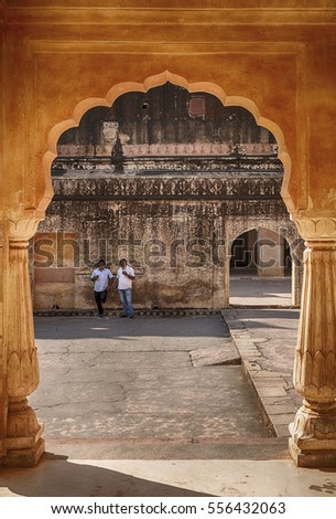 AMER, INDIA - NOVEMBER 18, 2016: Two men,leaning up against a wall, can be seen through an arch of the pavilion, or baradari, of the Man Singh Palace at the Amber Fort in Amer near Jaipur, India.