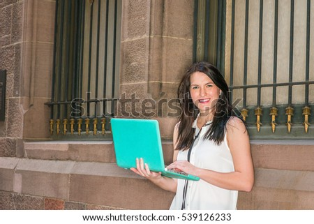 American female college graduate student studying in New York, wearing white sleeveless shirt, standing against vintage wall on street, working on laptop computer, smiling.