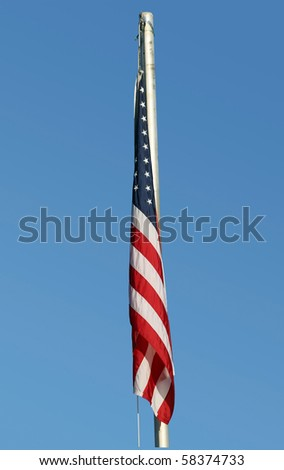 American flag hanging limply on calm, peaceful day with clear blue sky.