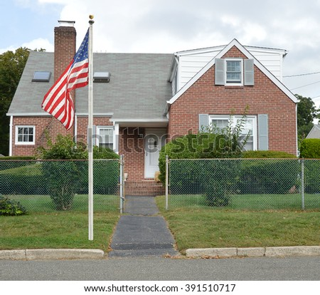 American Flag Pole Suburban Brick Bungalow Style Home with Chain Link Fence Blacktop Walkway Blue Sky Clouds Day Residential Neighborhood USA
