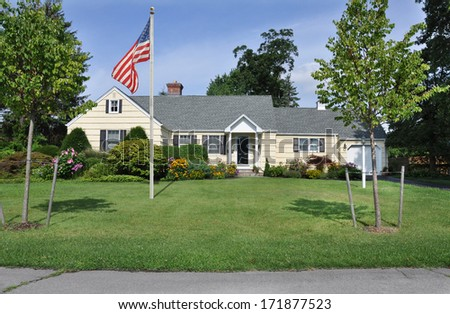American Flag pole suburban ranch style home landscaped flowers plants trees sunny blue sky day residential neighborhood usa
