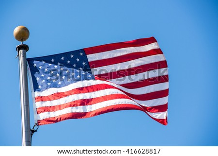 American flag waving with the wind on a clear blue sky.