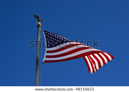 American flag, with globe and eagle, waving against blue sky, close up.