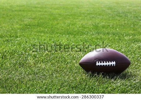 American football ball on green field