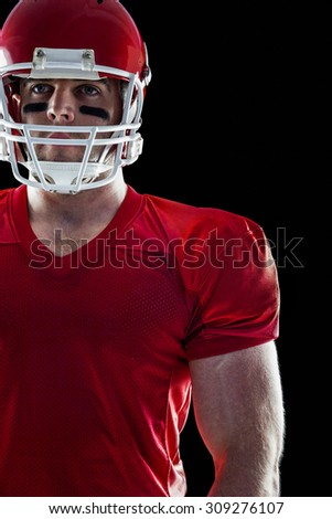 American football player looking at camera on black background