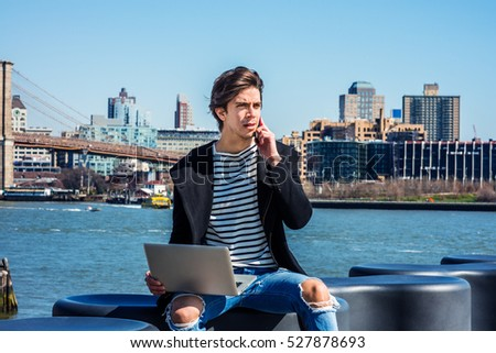 American man travels, works in New York, wearing fashionable long coat, striped undershirt, ripped broken hole jeans, frowned, works on laptop computer, calls on cell phone. Color filtered effect
