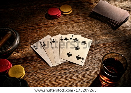 American West old gambler poker game with vintage playing cards showing a steel wheel straight flush hand on a weathered gambling wood table with wager tokens and whisky shot glass in a western saloon
