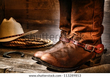 American West rodeo cowboy pair of traditional leather roper style western riding boots with authentic ranching spurs with hat and rope on an antique wood floor in an old ranch aged wooden barn