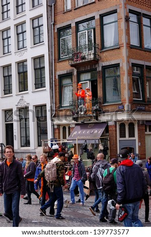 AMSTERDAM - APRIL 30: City natives and tourists celebrate Queen's Day, Dutch annual national holiday, in the streets of the city, on April 30, 2013 in Amsterdam, The Netherlands